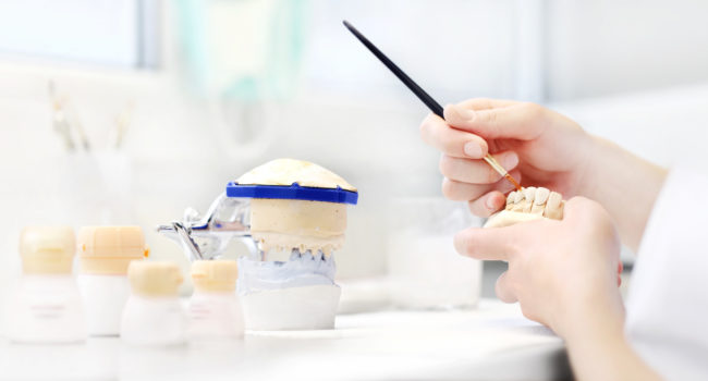 Dental technician hands working with tooth dentures in his laboratory, dental prostheses background concept, web banner